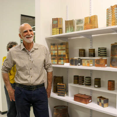 Peter Berry standing with a display of his ceramic work at the 2019 Holiday Show and Sale at the Ceramics Program, Office for the Arts at Harvard