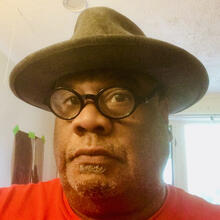African American man wearing glasses and hat