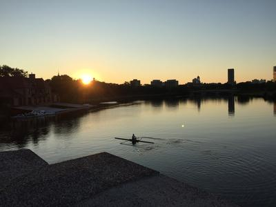 a person kayaks on the Charles River at sunrise