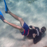 Student wearing Harvard shirt, giving thumbs up, snorkeling