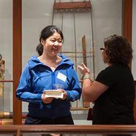 Two women talking in a gallery.