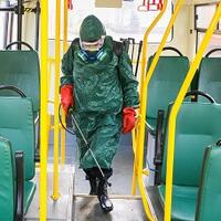 Suited man disinfects bus