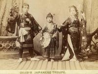 Sepia photograph of three members of the Okapis troupe wearing kimonos and posing with paper fans