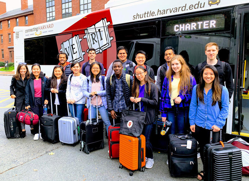 A group of twelve students and three instructors stand with their suitcases in front of a Harvard shuttle
