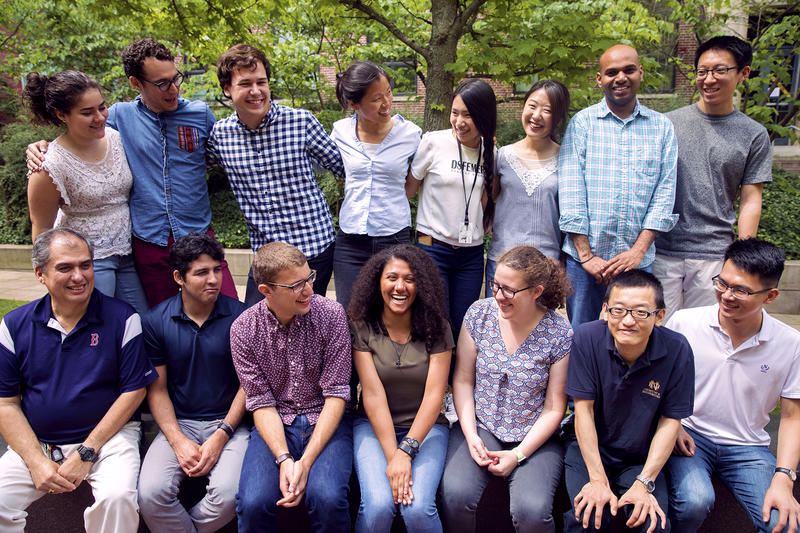 In front of green leaves and a brick building, Christina Woo stands in a row of her lab members with another row seated in front. The shot captures an informal moment: Woo and her diverse group of lab members smile and laugh, looking around at each other