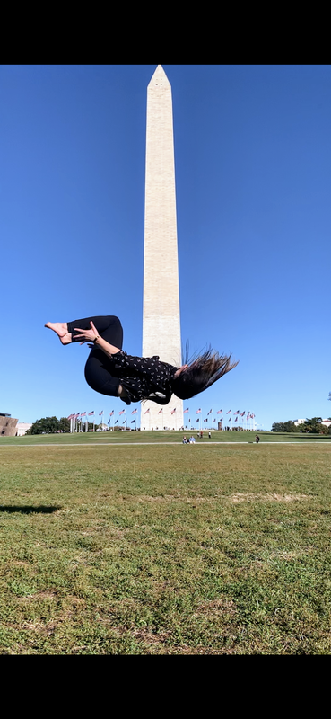 In mid-flip in front of the Washington monument, Michelle hangs perpendicular to the ground, her hair whipping toward the sky. She is barefoot, wearing black pants and a patterned blouse.