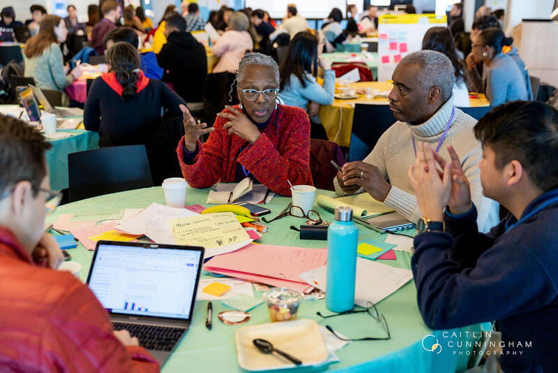 Participants design around colorful tables covered in notepads, sticky notes, and coffee. Approximately 200 people gathered from businesses and schools across the city to create 28 solutions that hack for inclusion.