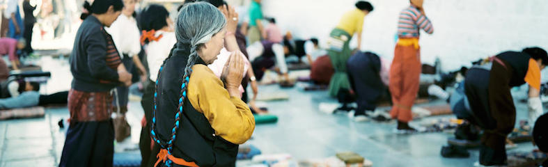 A Tibetan woman kneels in prayer