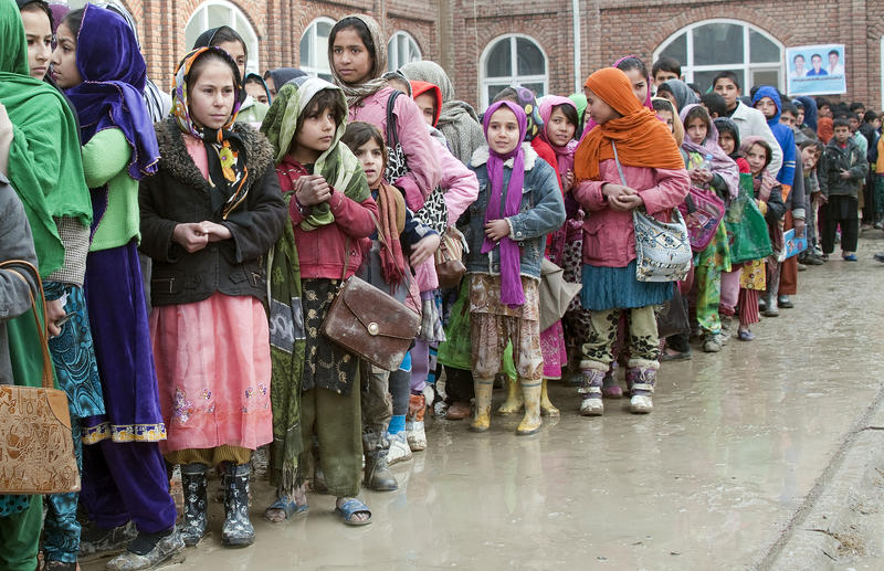 Kabul refugee children stand in line to receive aid