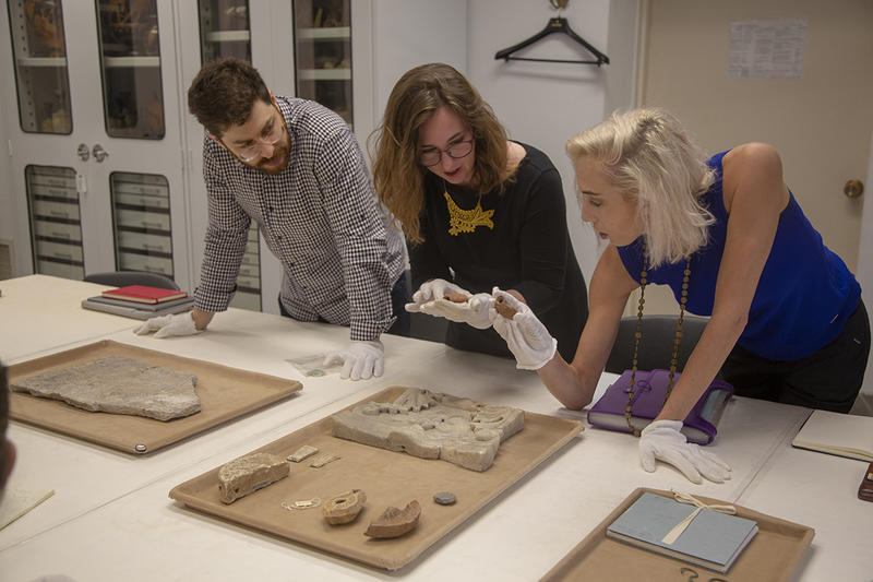 From left, Students Omri Matarasso (Princeton), Sarah Porter (Harvard), and Rebekah Haigh (Princeton) inspect pilgrimage ampullae. Photo by Julie Clack, Princeton University.