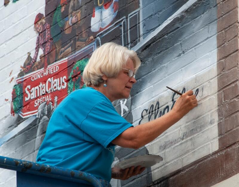 Artist Ellen Elmes signing the Kingsport, Tennessee history mural. Photo by Don Elmes