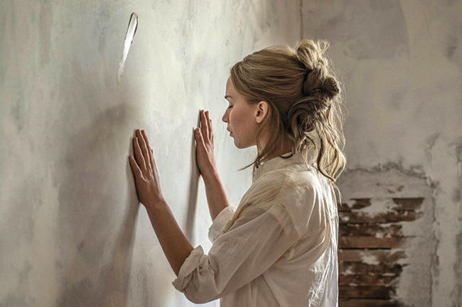 "Film still from ""mother!"" with the Mother character standing with hands gently placed on the house's bare wall"
