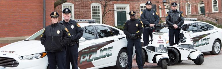 Image of 5 Officers Standing in Front of 2 Police Cruisers