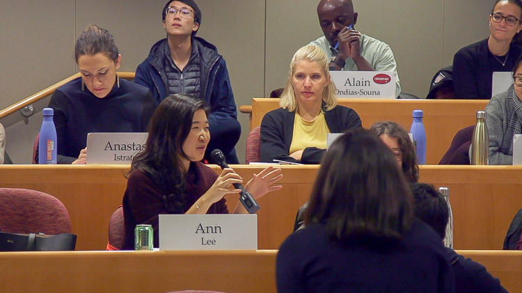 "Medium close up of student with name card ""Ann Lee"" speaking into microphone. Other students watch and listen. Back of Professor Battilana's head is visible in foreground."