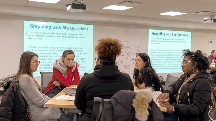 "Five graduate students seated at a table in discussion. Projected on the screen behind them are slides that read ""Grappling with Big Questions"" and then smaller texts beneath."
