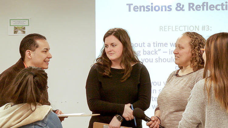 "Four graduate students and Instructor Brion-Meisels standing together in a small group in discussion. There is a section of a projected slide visible behind them that reads ""Tension & Reflections."""