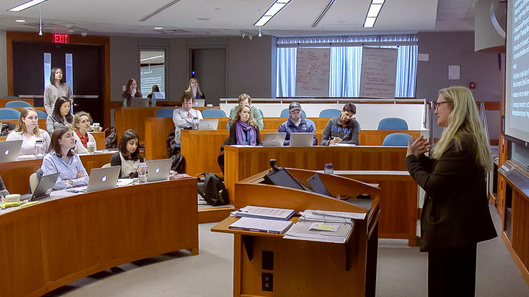 Side shot of Professor Grotzer at the front of the classroom and students listening.