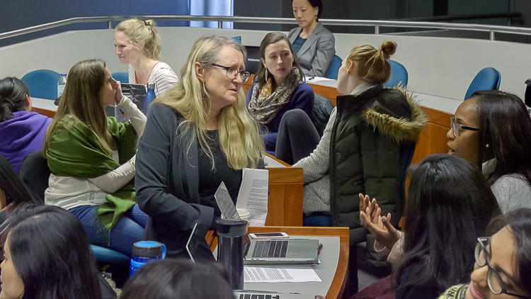 Professor Grotzer joining in on small group discussion. Graduate students in foreground and background engaged in discussion.