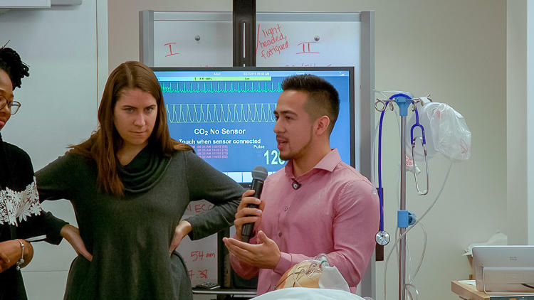 Close up of two graduate students, one speaking into a microphone. Around the students are medical monitors and machines.