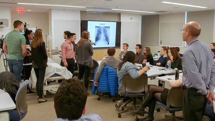 Wide shot of classroom with some students seated and some students gathered around a fake patient on a hospital bed hooked up to machines.