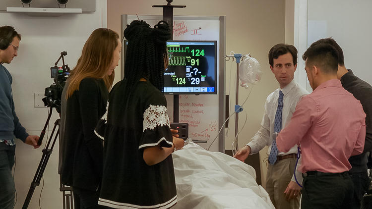Medium close up of a group of students in a classroom gathered around a pretend patient on a hospital bed, hooked up to monitors.