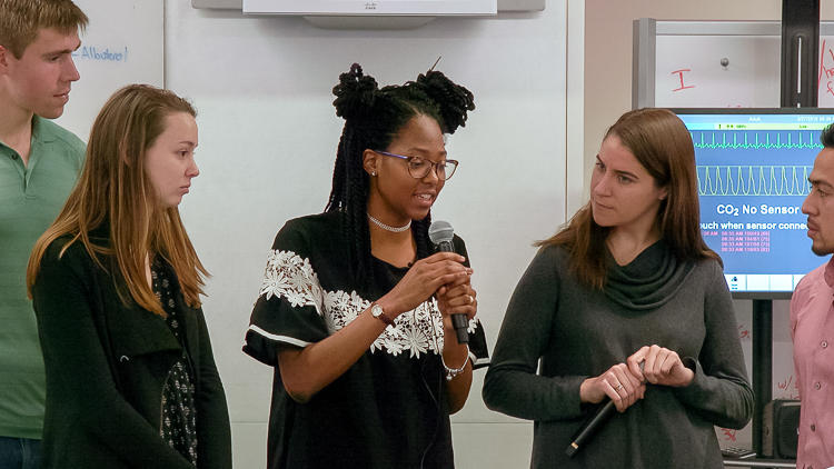 Close up of graduate student speaking with microphone in a group of 4 other students.