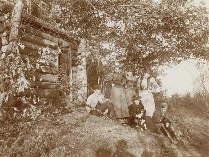 Group of people in front of cabin.