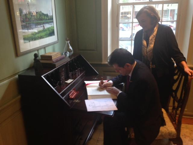 Ambassador Pangrazio signs the university guest book at Wadsworth House as Jackie O'Neill looks on