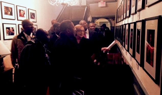 Jackie O'Neill points out notable photos from past Harvard Commencements to visitors from Ghana and Nigeria at Wadsworth House