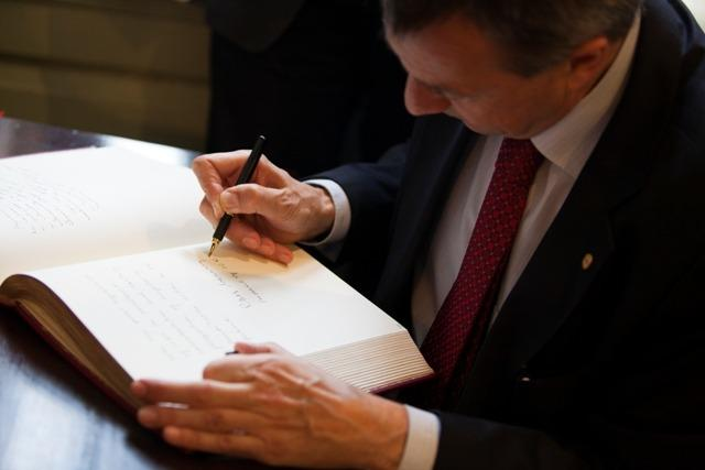 Peter Maurer, President of the ICRC, signs the University guest book