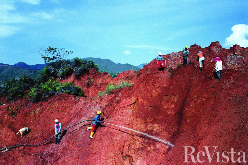 A group of miners, members of several families who have owned land in Yolombó for centuries, direct jets of water at the hill to form a channel of red mud at its base.