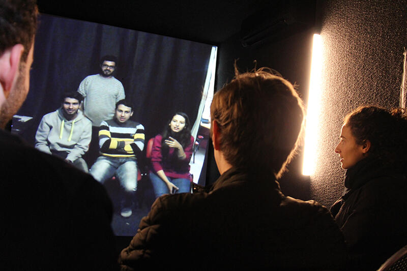 Photo of several students chatting with four refugees via video conference