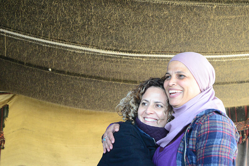 Two women hugging each other and smiling