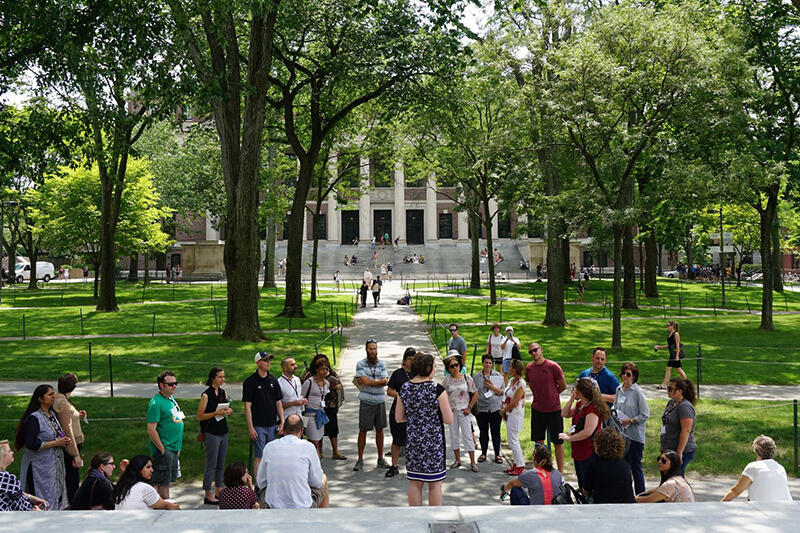 Students gathered outside the Memorial Church in Harvard Yard with Widener library in the background