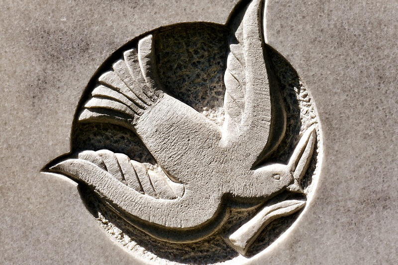 Dove flying with an olive branch, carved into stone