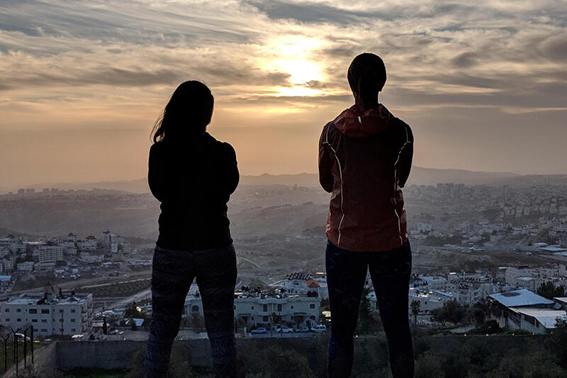 Two students looking out at a city landscape, silhouetted by the sunset