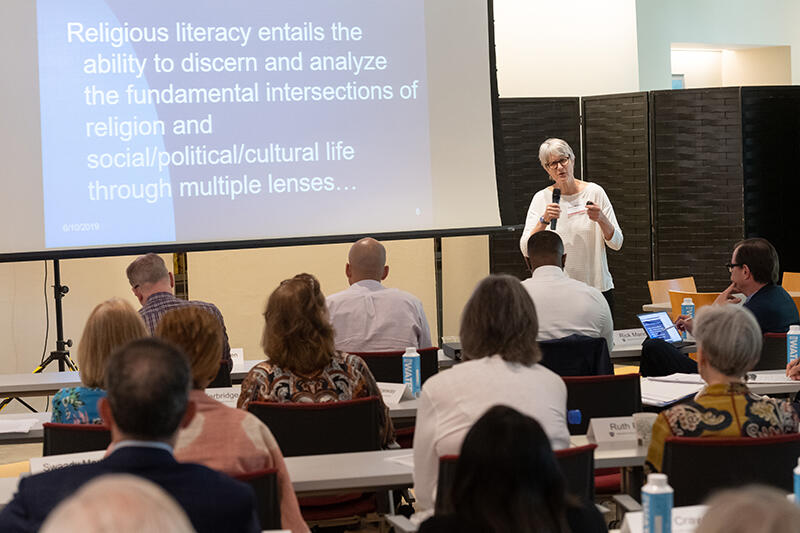 Dianne Moore teaching class with powerpoint screen showing Religious Literacy definition