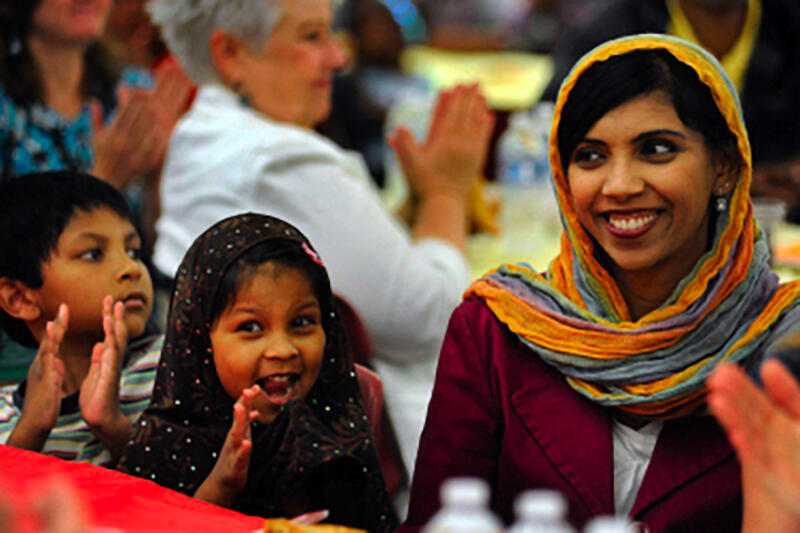 Muslim woman with children sitting at a table