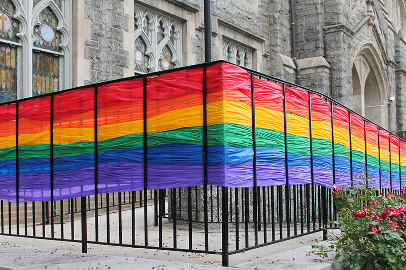 Rainbow banner woven into fence surrounding a church