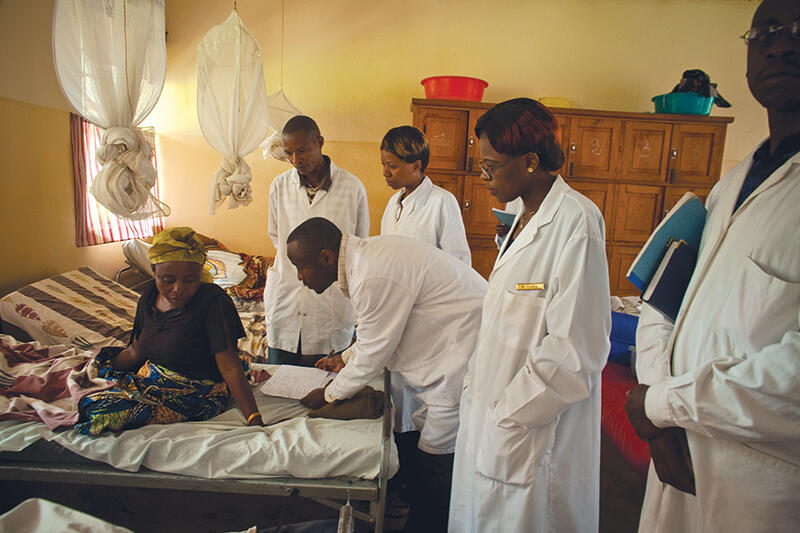 Doctors examine a woman in an African clinic setting