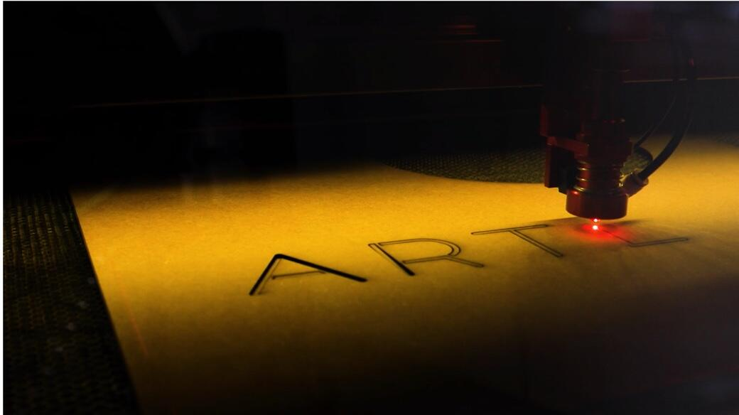 Laser cutter engraving a plank of wood with the letters, A, R, T.