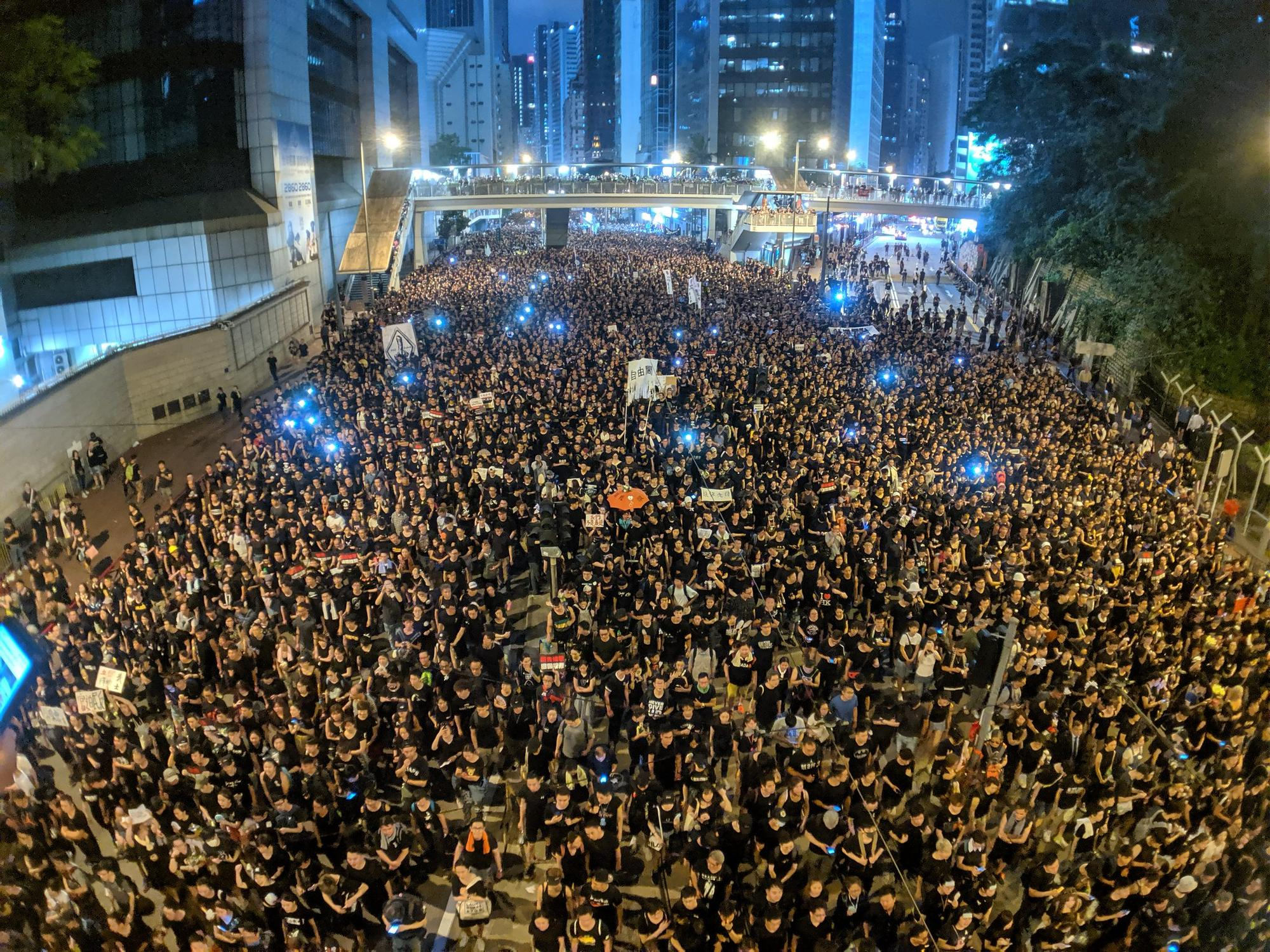 People with signs, some holding up lights, fill the streets of Hong Kong at night to protest