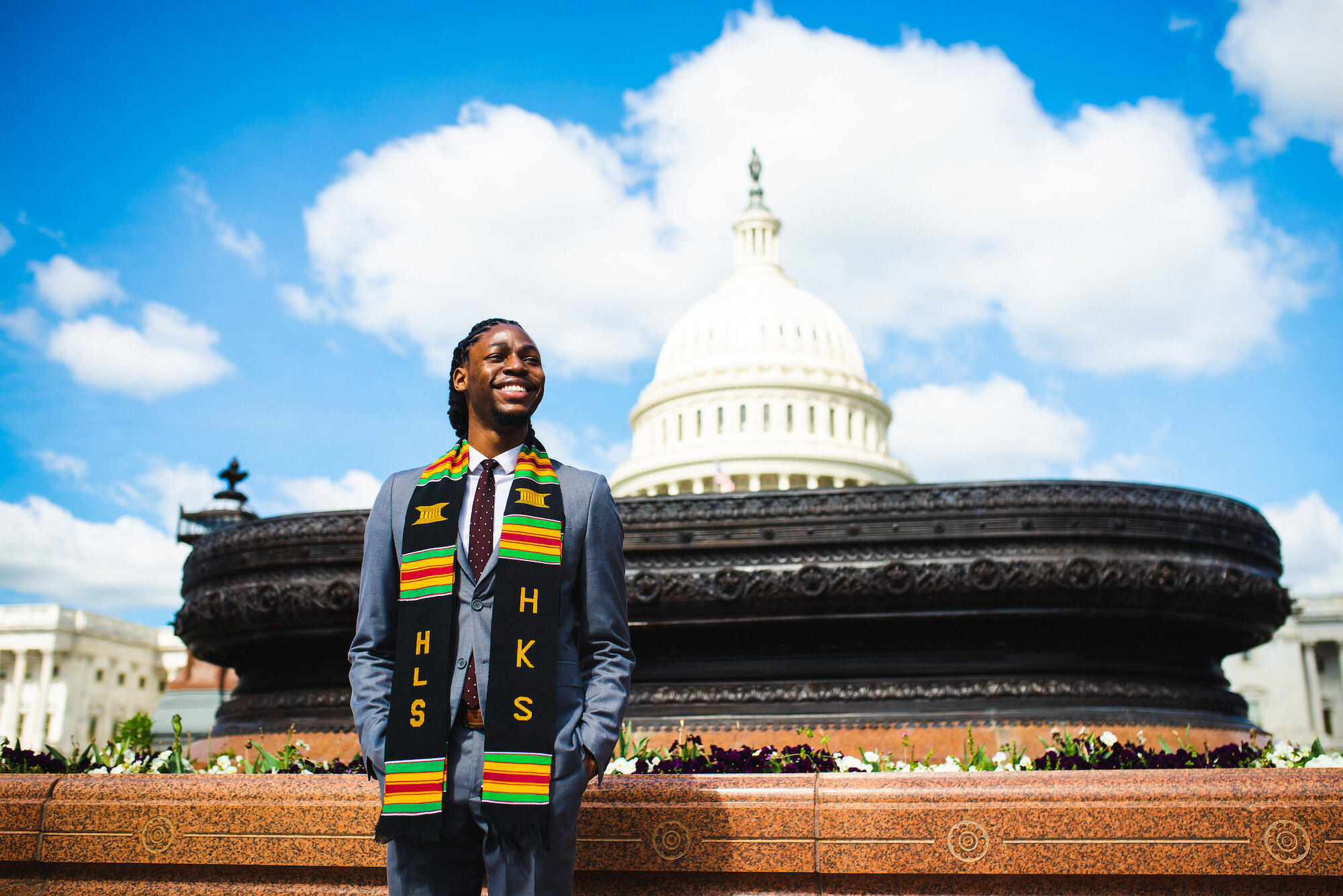 Johnson stands with his graduation stole in front of Capitol Hill