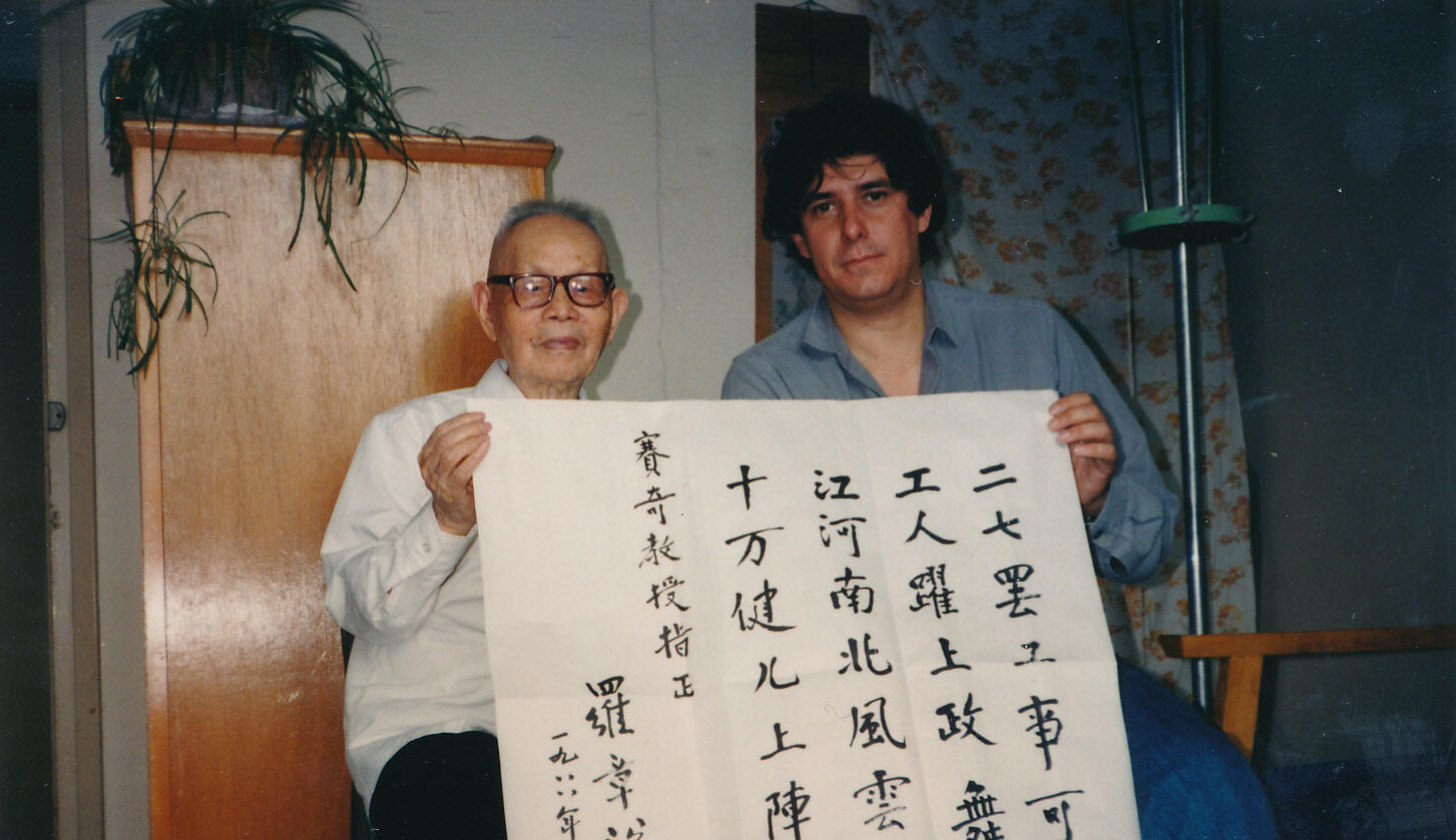Tony Saich sits next to an older man holding a Chinese language poster