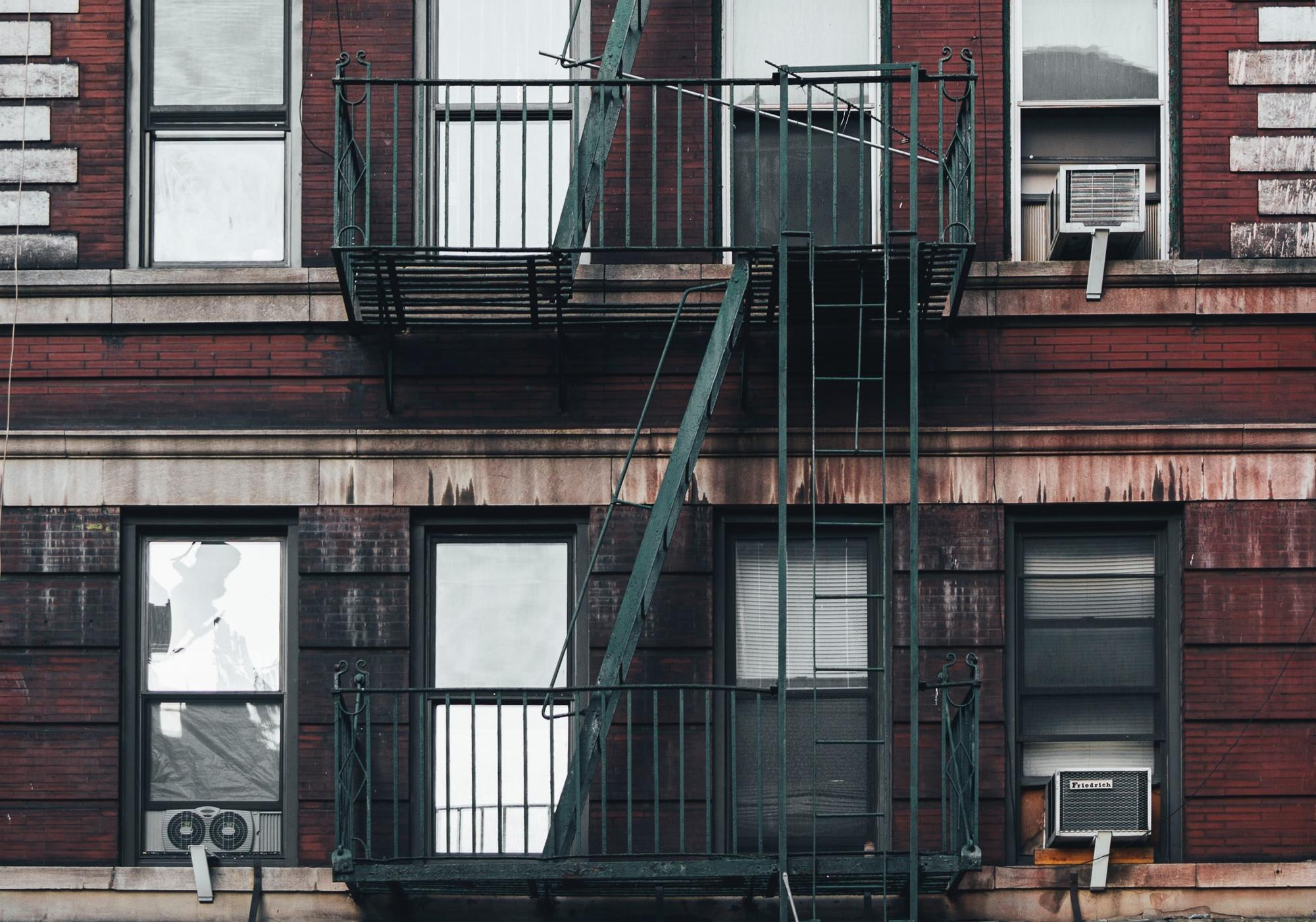 Two floors of New York City apartments, windows hold air conditioning units