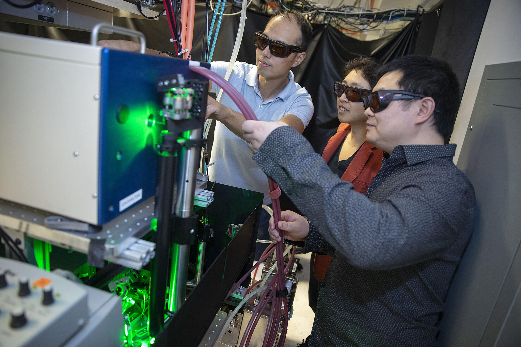 A photo of Kang-Kuen Ni, Ming-Guang, and Yu Liu standing at their wire-filled machine in the lab