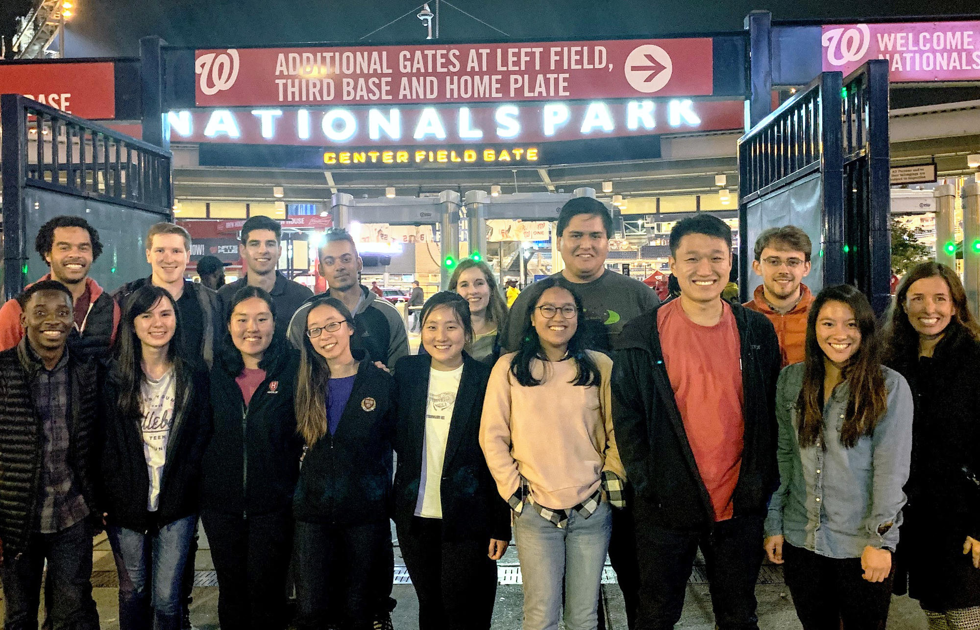 The whole group wears warm, casual clothes, standing outside bright lights advertising the Nationals baseball park at night. The group stayed nearby, but the Nationals were playing an away game in Houston.