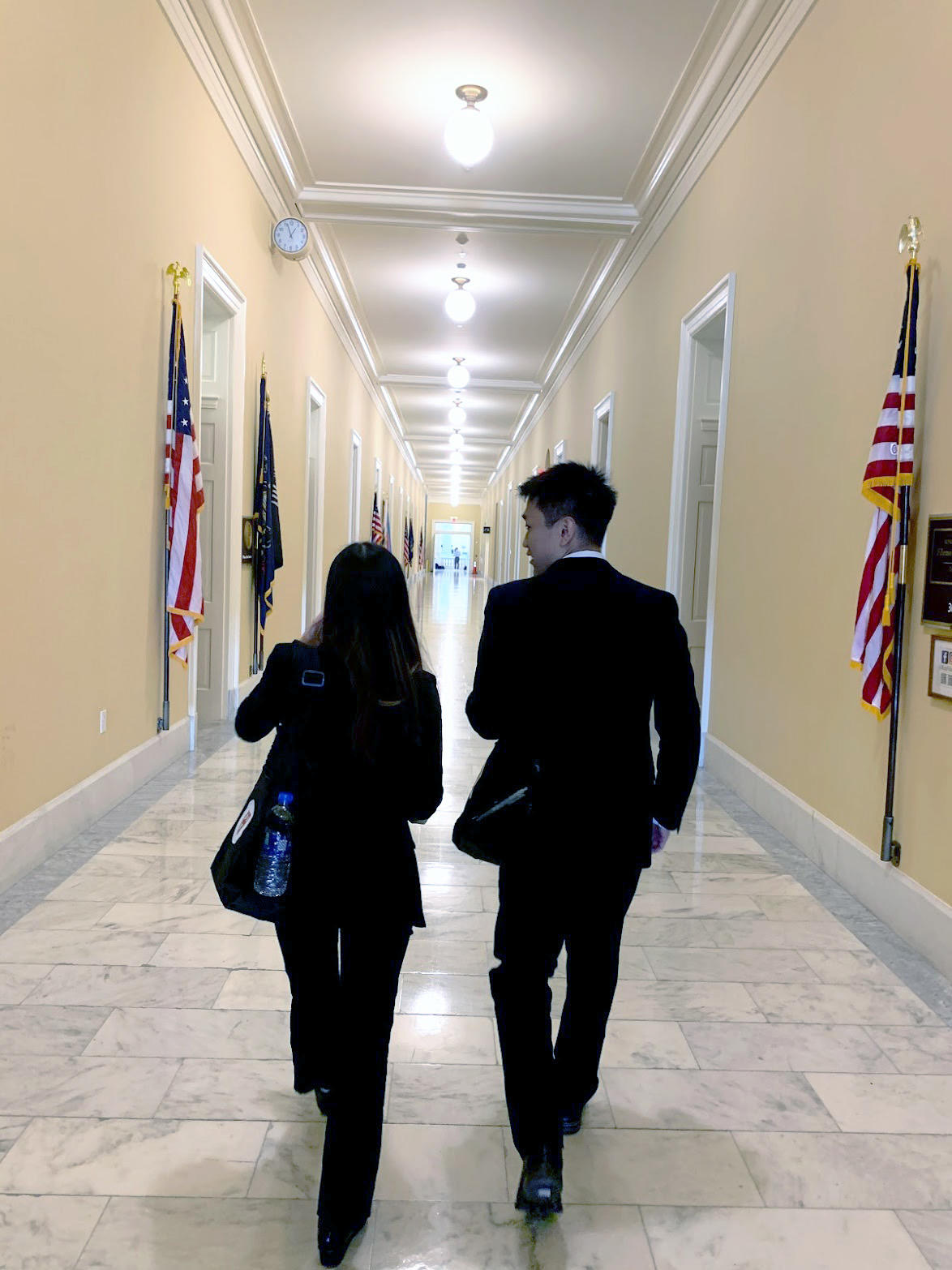 Both in black suits, Stephanie and Eugene walk away from the camera, down a hallway with white marble floors, soft yellow walls, and American flags stationed against the walls.
