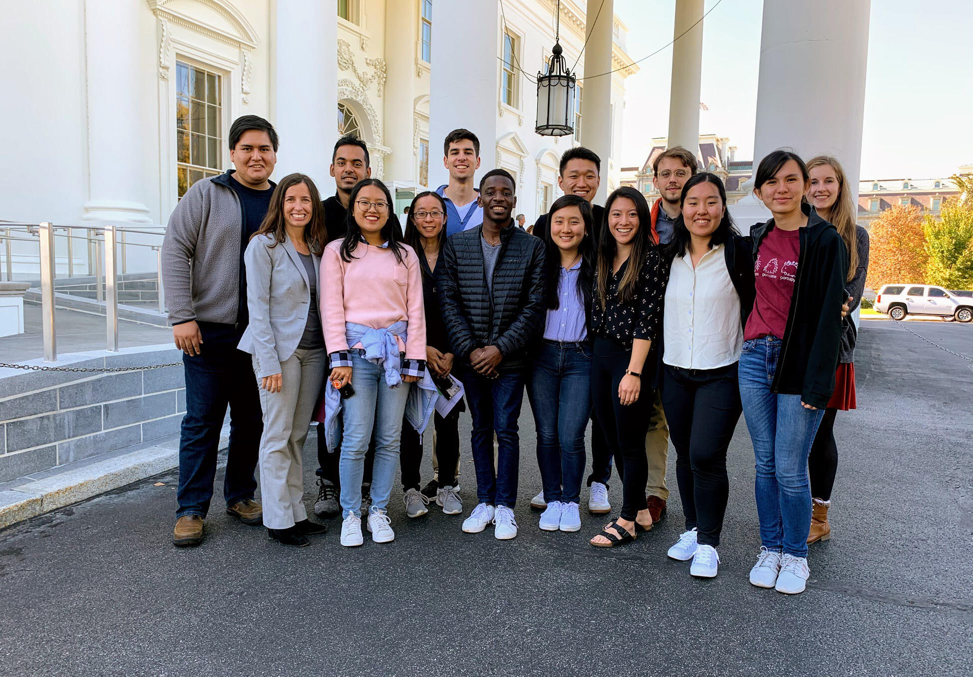 The group wears casual clothes, posing next to an entrance to the White House