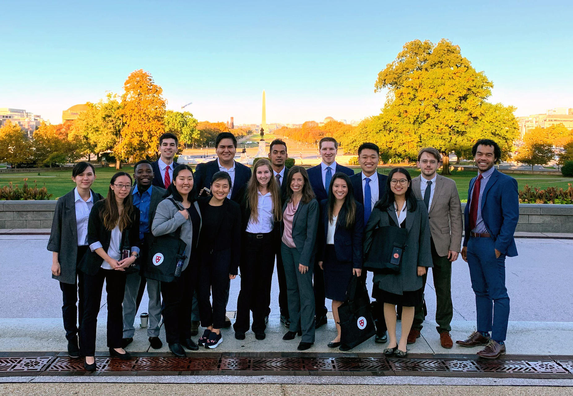 Chemistry students and teachers pose in their suits for a photo on the National Mall, the Washington monument like a glowing needle in the background